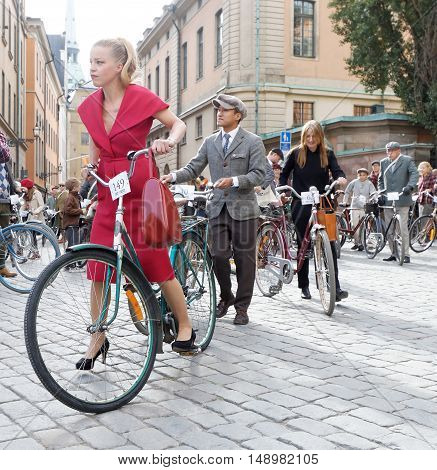 STOCKHOLM - SEPT 24 2016: Beautiful woman dressed in old fashioned red dress cycling in the Bike in Tweed event September 24 2016 in Stockholm Sweden