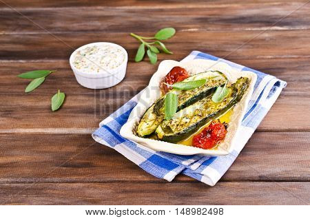 Baked zucchini with tomatoes and sage. Selective focus.