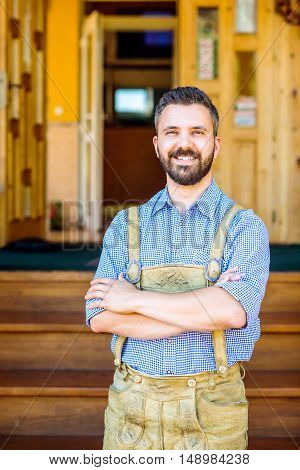 Handsome hipster young man in traditional bavarian clothes, arms crossed against old wooden rural house. Oktoberfest.