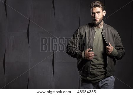 Man With Beard In Green T-shirt On Gray Cement Background