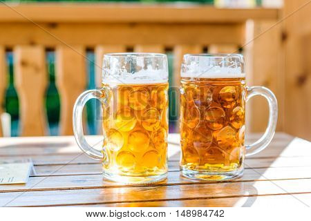 Two mugs of beer laid on wooden table, sunny day