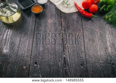 Vegetable, oil, pita and condiments frame on dark wood