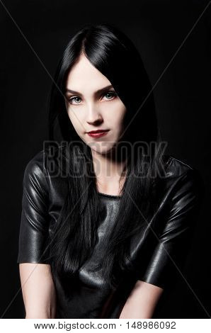 Gorgeous brunette with white skin red lips long black hair transparent eyes on black backdrop looking mysterious and sexy