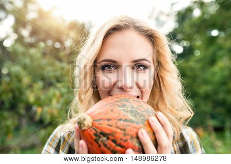 Beautiful young blond woman in checked shirt working in her garden harvesting pumpkins. Autumn nature.