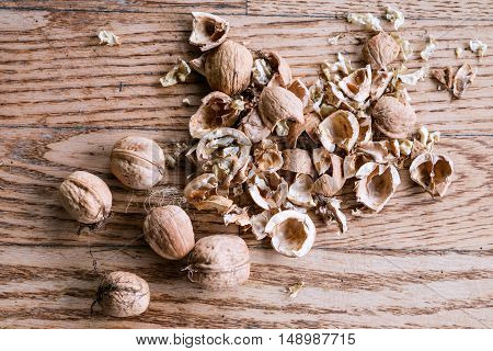 Heap of cracked and whole walnut fruits on wooden background. Studio shot.