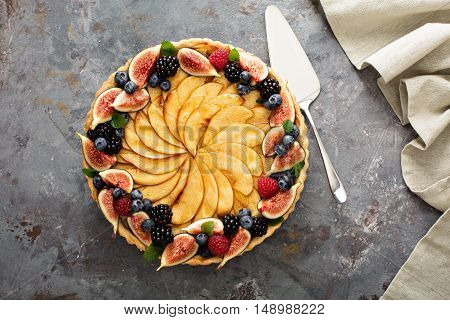 French apple tart decorated with fresh berry and figs overhead shot
