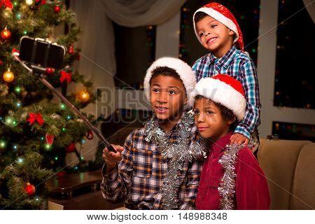 Three boys take Christmas selfie. Kids take selfie on Christmas. Moment worth capturing. Good mood for Christmas photo.