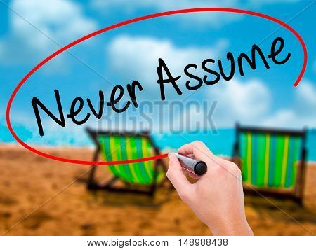 Man Hand Writing Never Assume With Black Marker On Visual Screen.