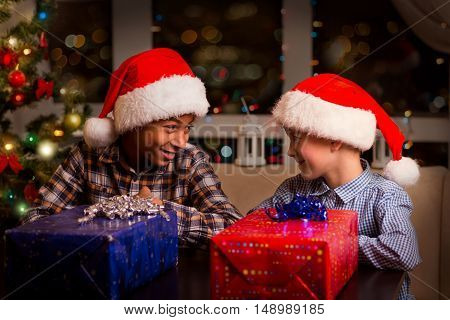 Smiling boys beside Christmas presents. Two kids near Christmas presents. You know what I mean. I have and idea.