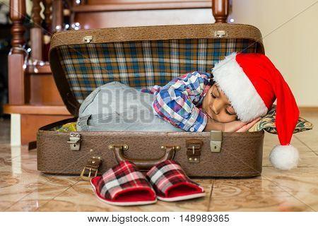Black boy sleeps in suitcase. Little santa sleeps inside suitcase. New day is waiting. Definition of peacefulness.