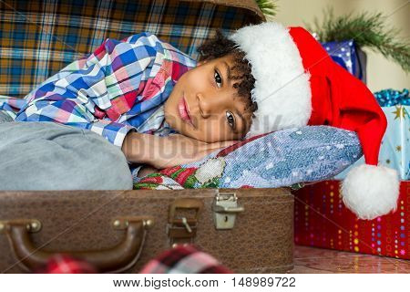 Little santa laying beside presents. Kid inside suitcase near presents. Surprise is so close. Dreams come true on holidays.
