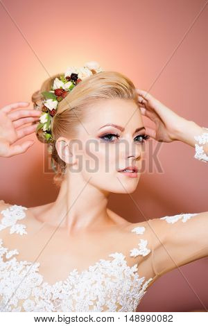 young sexy woman or girl bride with flowers in stylish blonde hair and fashionable makeup on pretty face in white lace wedding dress in studio on pink background