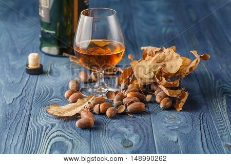 glass with whiskey on blue wooden table