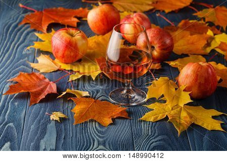 Cognac and apples fruit on blue table