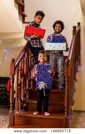 Black children holding Christmas presents. Boys hold presents on staircase. Everyone say cheese. Moment to remember.