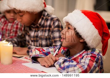 Children writing letter to Santa. Afro kids write Christmas letter. Making a Christmas wish list. Think about best presents.