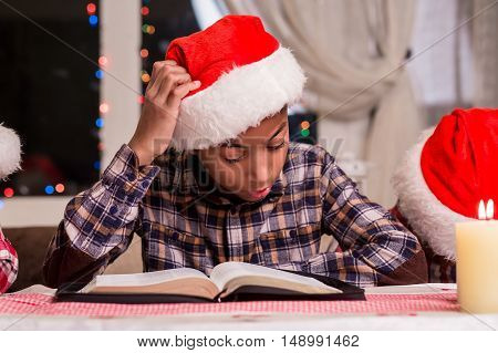 Little Santa reads a book. Boy reading book on Christmas. Reading Christmas stories beside window. Kid's leisure time on holidays.