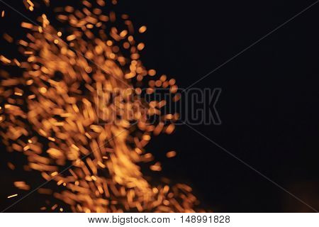 blurred firecamp sparks over night sky, black background