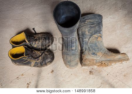 Photo of dirty shoes boots and clothes of worker during renovation apartment