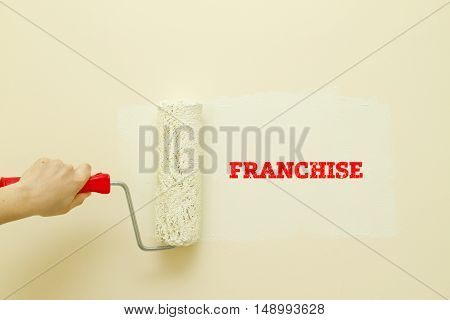 Woman hand painting wall written FRANCHISE word on it.