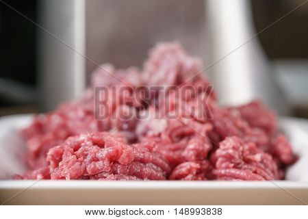 freshly minced beef with purple onion on kitchen table, shallow focus