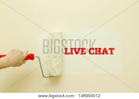 Woman hand painting wall written LIVE CHAT word on it.