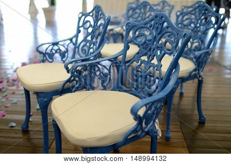 Beautiful chairs in wedding restaurant for marriage. White decor for bride and groom. Colorful decoration for celebration. Beauty bridal interior