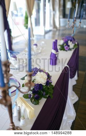 Beautiful wedding restaurant for marriage. White decor for bride and groom. Colorful decoration for celebration. Beauty bridal interior. Bouquet and flowers in hall