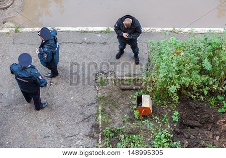 SAMARA RUSSIA - SEPTEMBER 22 2016: Russian police stand near old rusty artillery shell found in digging trenches