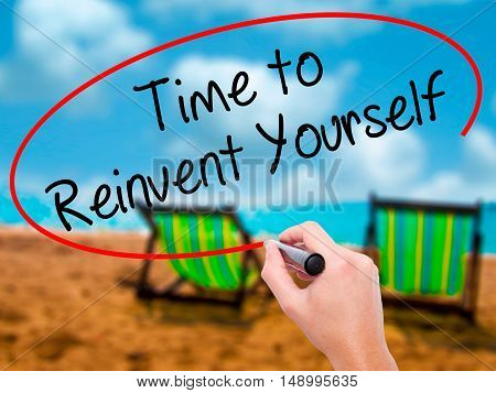 Man Hand Writing Time To Reinvent Yourself With Black Marker On Visual Screen