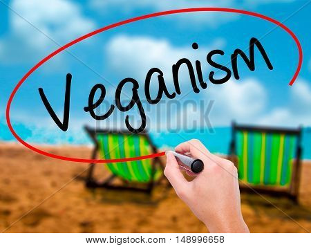 Man Hand Writing Veganism With Black Marker On Visual Screen