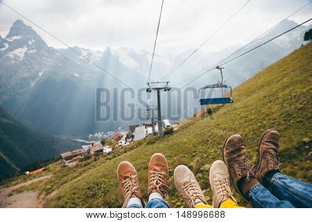 Family on cableway in mountains, feet over alpine view