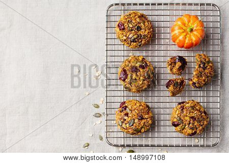 Oat cookies with cranberries and maple glaze on a colling rack. Rustic textile background. Copy space. Top view