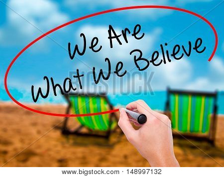 Man Hand Writing We Are What We Believe With Black Marker On Visual Screen
