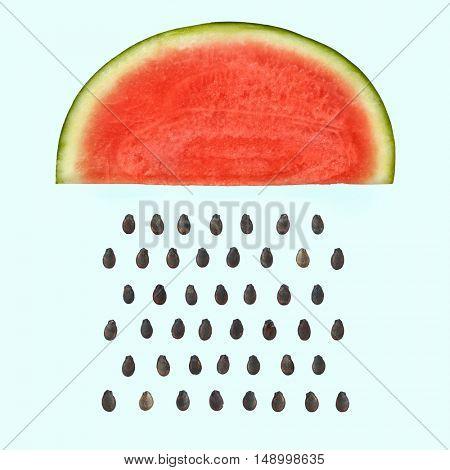 Watermelon slice with seeds raining.