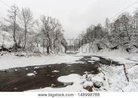 Dark river in the winter mountain forest. Karpaty Ukraine