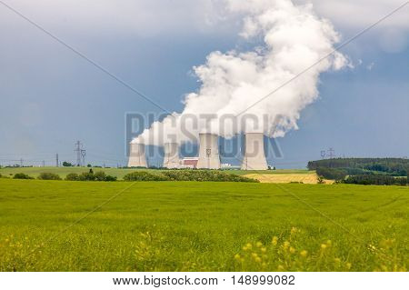 Thermal power plant, green field with with blue sky