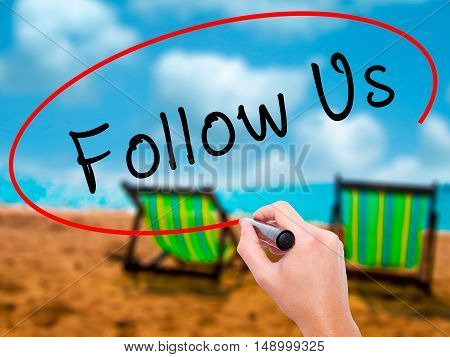 Man Hand Writing Follow Us With Black Marker On Visual Screen