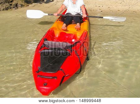 Cropped image of woman kayaking red kayak on a summer day.
