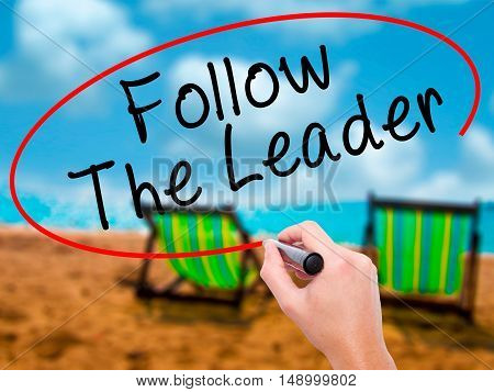 Man Hand Writing Follow The Leader With Black Marker On Visual Screen