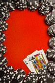 Black poker chips on red felt with Blackjack (21) hand