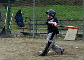 picture of little-league  - Young boy up for bat and hits a home run - JPG