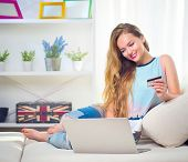 Beauty young woman holding credit card and using laptop for Online shopping, e-shopping. Beautiful g poster