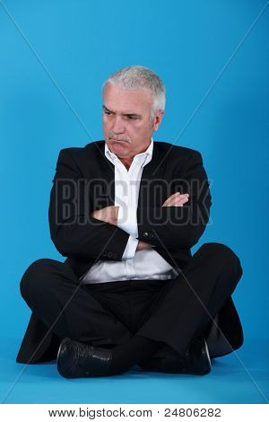 angry senior businessman sitting cross-legged
