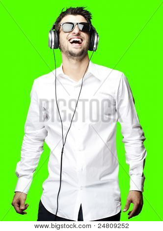 portrait of young man listening to music over removable chroma key background