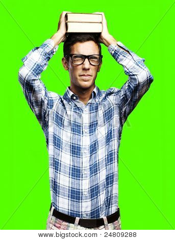 portrait of young man holding books pile on his head against a removable chroma key background