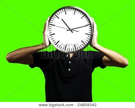 portrait of man holding clock over his head against a removable chroma key background