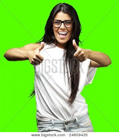 portrait of young woman doing good symbol against a removable chroma key background