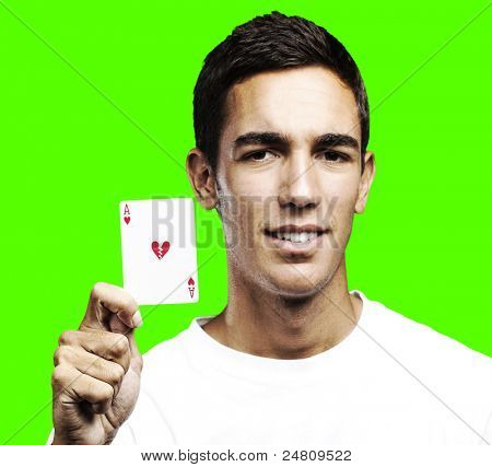 portrait of young man holding a poker broken heart symbol card against a removable chroma key background