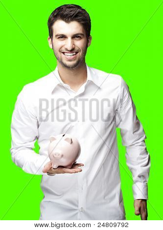 portrait of young man holding a piggy bank over removable chroma key background